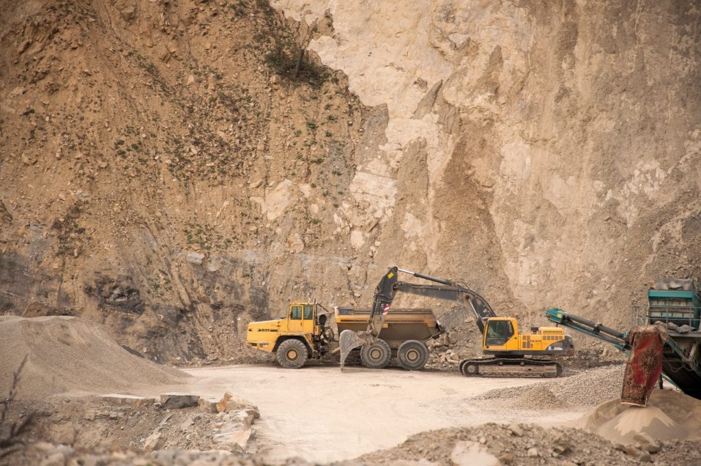 Excavator near industrial machines